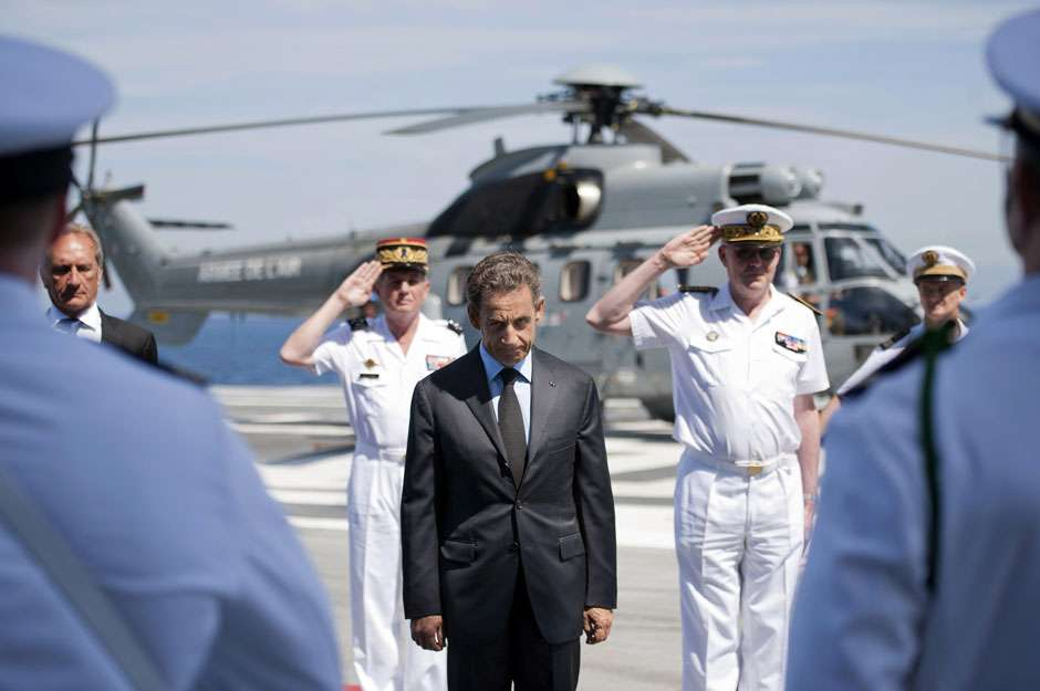 France's President Sarkozy reviews the troops on the deck of the aircraft carrier Charles de Gaulle